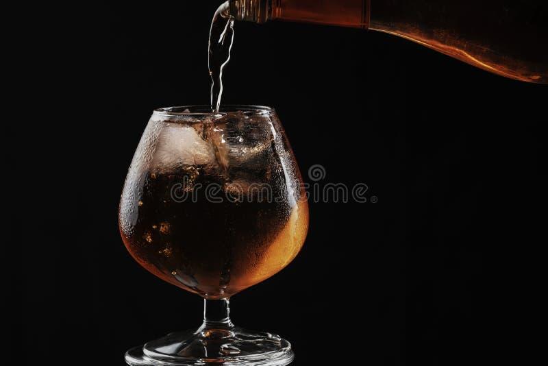 Whisky wird in ein Weinbrandglas mit Eis gegossen, ist das Glas voll und geschwitzt stockfoto