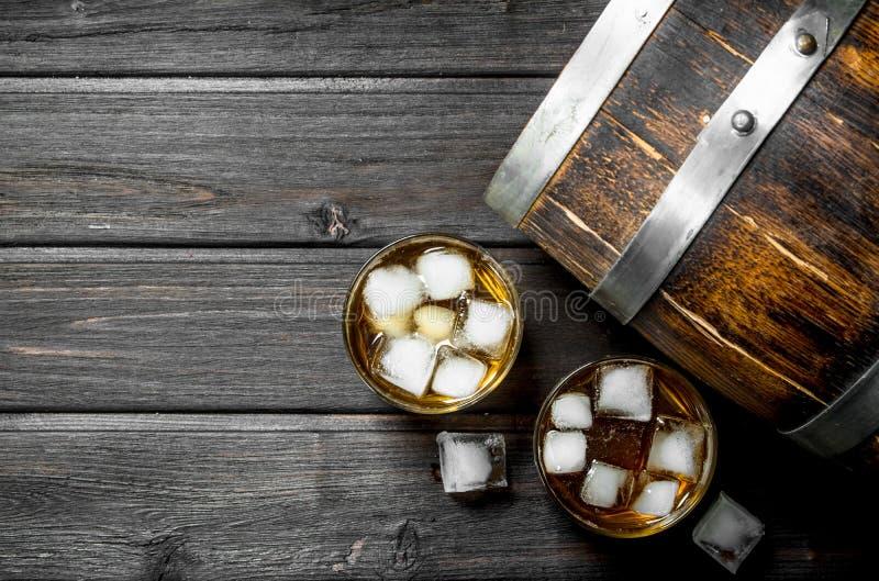 Whisky z lodem i drewnianą baryłką zdjęcie stock