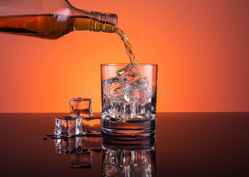 Whiskyalkohol, der in Glas mit Eisgetränk auf orange Hintergrund ausläuft stockbilder