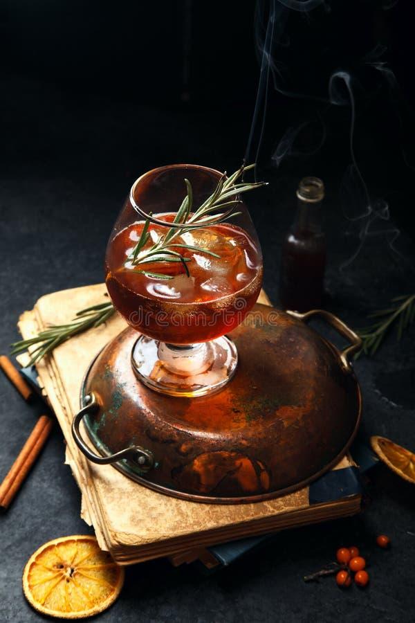 Whiskycocktail mit Eis und gebranntem Rosmarin lizenzfreies stockfoto
