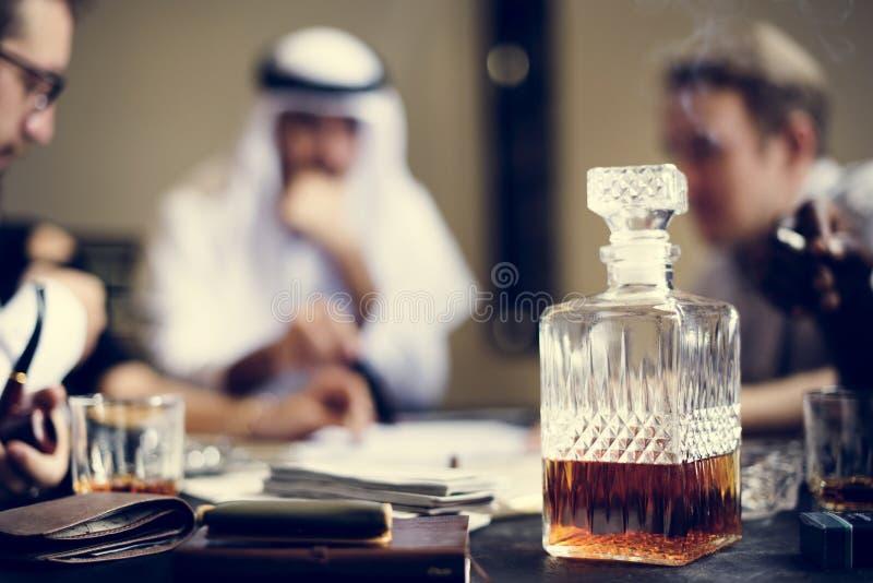 Whiskydekantiergefäß mit Geschäftsleuten im Hintergrund stockbilder