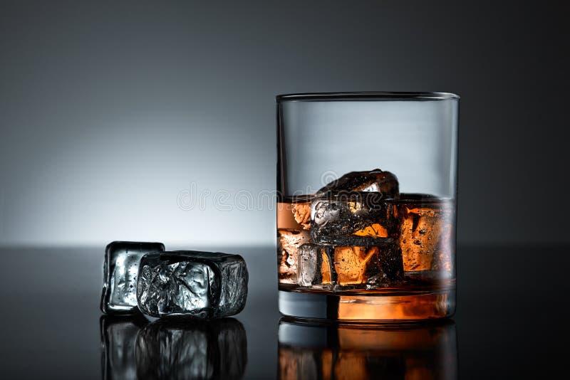 Whiskyexponeringsglas med iskuber arkivbilder