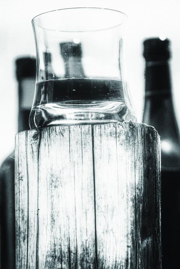 Whiskyexponeringsglas på träställning arkivbilder