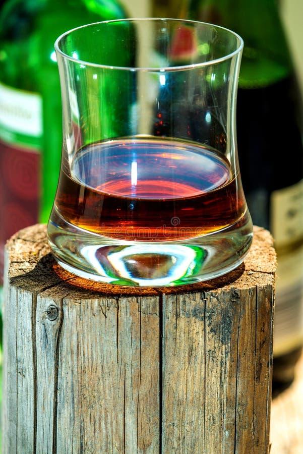 Whiskyexponeringsglas på träställning royaltyfria foton