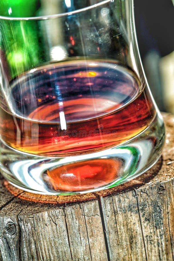 Whiskyexponeringsglas på träställning arkivbild
