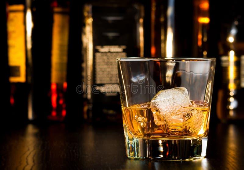 Whiskyglas mit Eis vor Flaschen stockfotografie