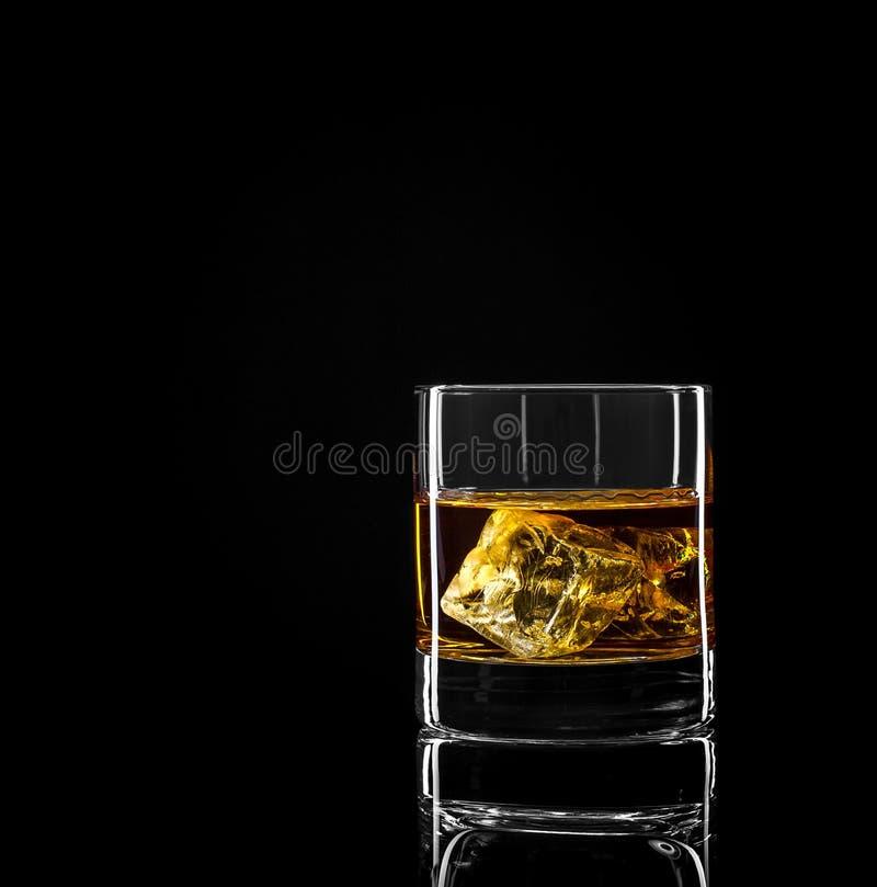 Whiskyglas mit goldenem Alkohol- und Eiswürfel stockfoto