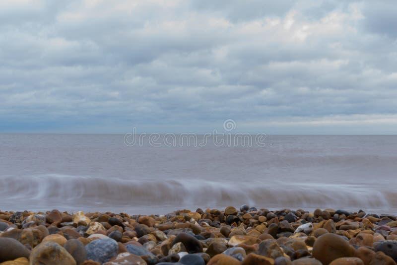 Whispy ondeggia l'esposizione lunga sulla spiaggia di Felixstowe fotografie stock