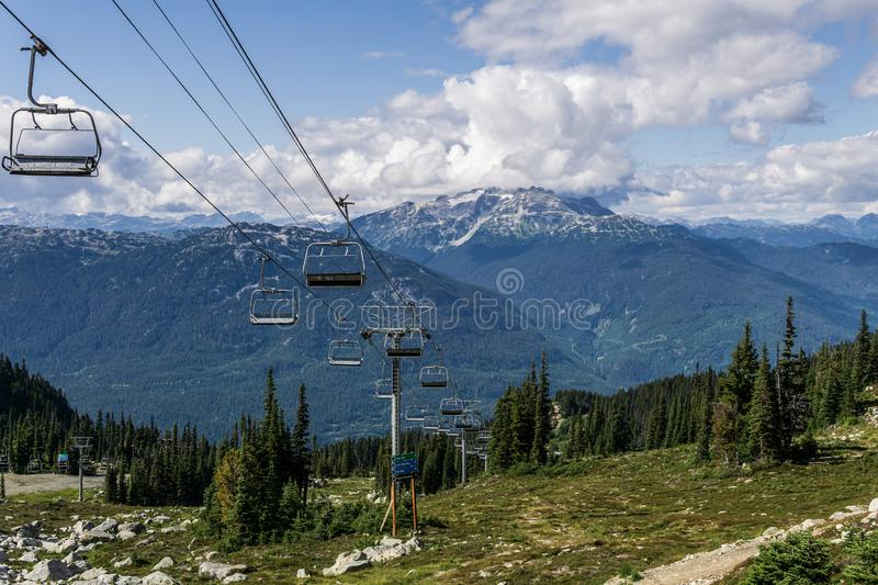 WHISTLER, CANADA - AUGUST 25, 2019: chair lift ride to the top of the mountain. Cable, grass, green, season, sky, summer, vacation, view, chairlift, forest royalty free stock image
