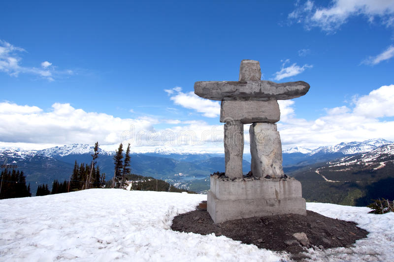 Whistler Peak inukshuk with snow and mountains royalty free stock photos