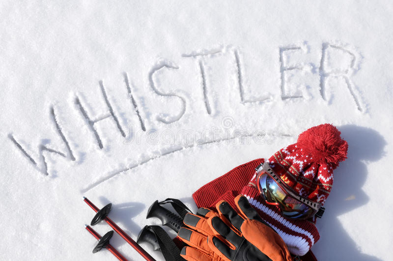 Whistler ski vacation winter sports concept, skiing equipment, word written in snow. The word Whistler written in snow with ski poles, goggles and hats stock photo