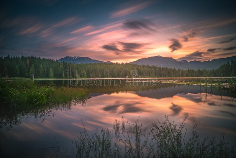 Whistler sunset clouds and reflections. This is a long exposure of the Lost Lake sunset at Whistler, BC Canada royalty free stock photo