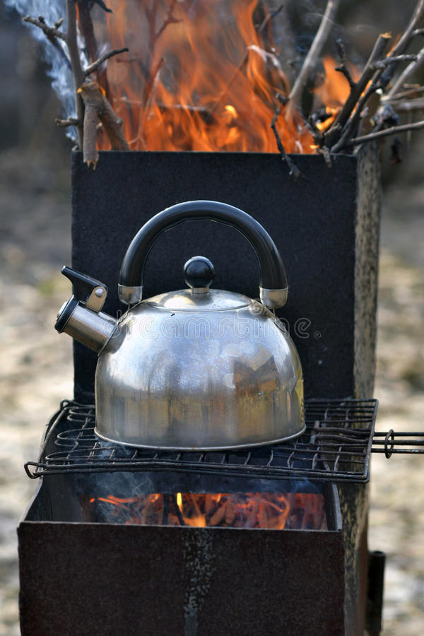 The whistling kettle begins to boil on a brazier.  royalty free stock image