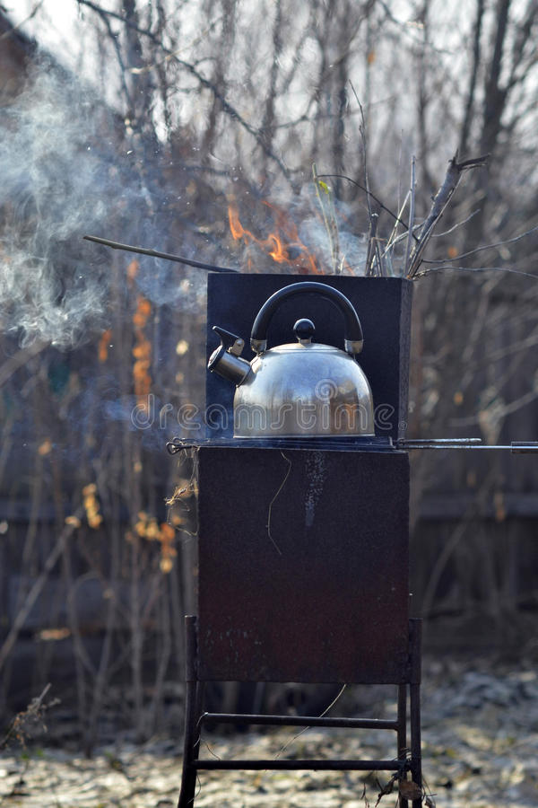 The whistling kettle begins to boil on a brazier.  royalty free stock photography