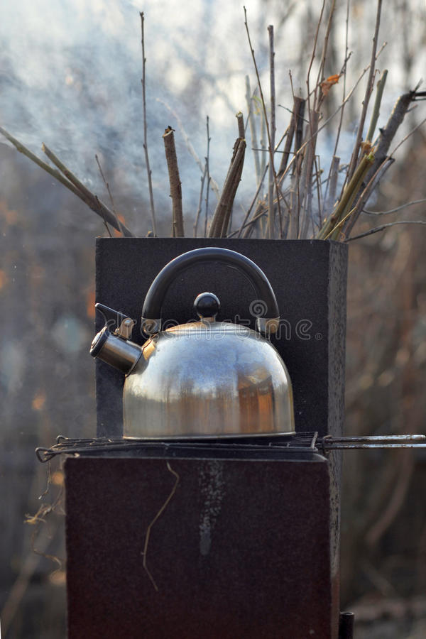 The whistling kettle begins to boil on a brazier. The whistling kettle begins to boil on a brazier stock photo