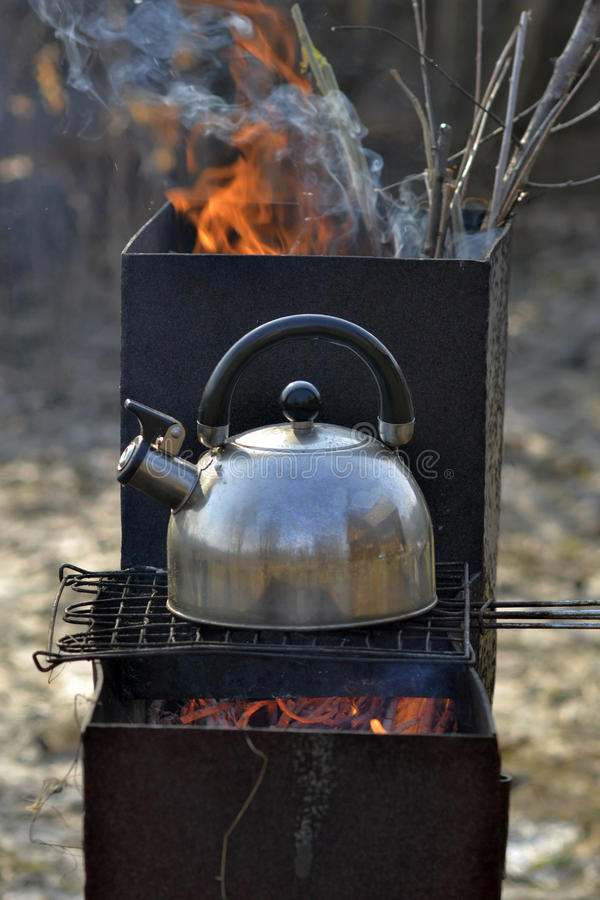 The whistling kettle begins to boil on a brazier. The whistling kettle begins to boil on a brazier royalty free stock photos