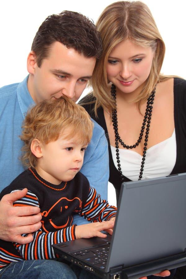 Whit van ouders de zoon kijkt op notitieboekje royalty-vrije stock fotografie