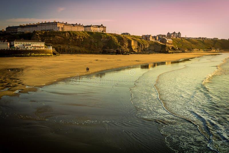 WHITBY в АНГЛИИ Люди идя на пляж Whitby на точный солнечный, ветреный день В Whitby, северный Йоркшир, Англия стоковые изображения