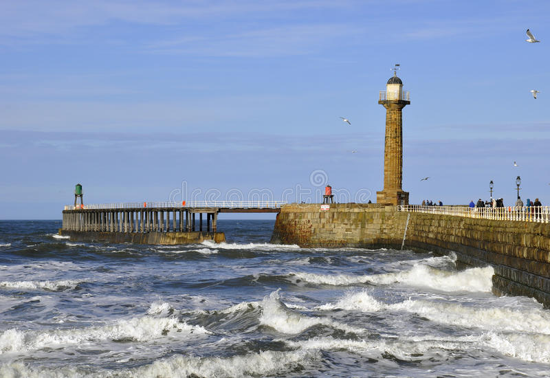 Whitby pier and lighthouse royalty free stock photo