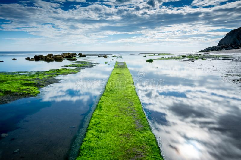 Whitby sky reflection in water near east cliffs, North Yorkshire, England stock image