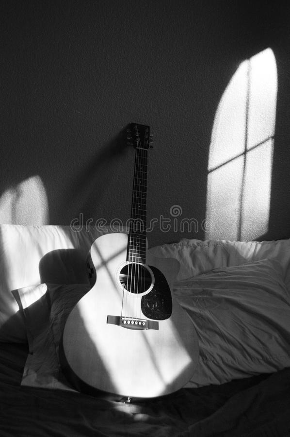 White Acoustic Guitar on Grey and White Textile stock image