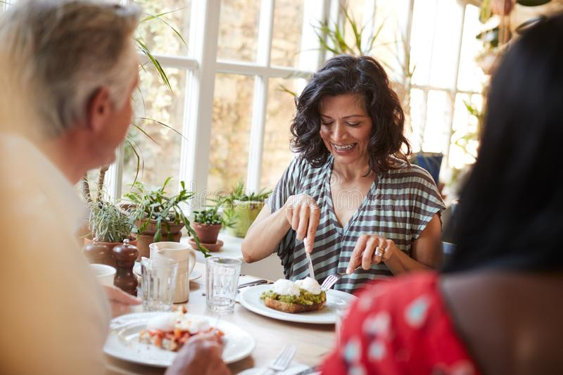 White adult woman eating with friends at a cafe, close up royalty free stock image