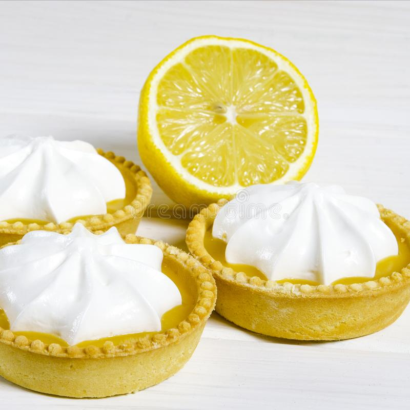 White aircake with lemon filling and lemon on a wooden table. Lemon meringue pie. small lemon meringue pie dessert shortcrust pastry with lemon custard filling stock photo