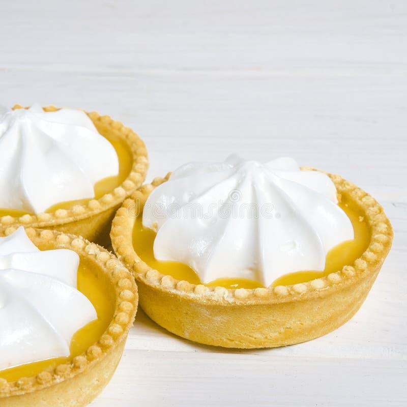 White aircake with lemon filling and lemon on a wooden table. Lemon Meringue Pie. Small Lemon Meringue Pie Dessert Shortcrust Pastry with Lemon Custard Filling stock image
