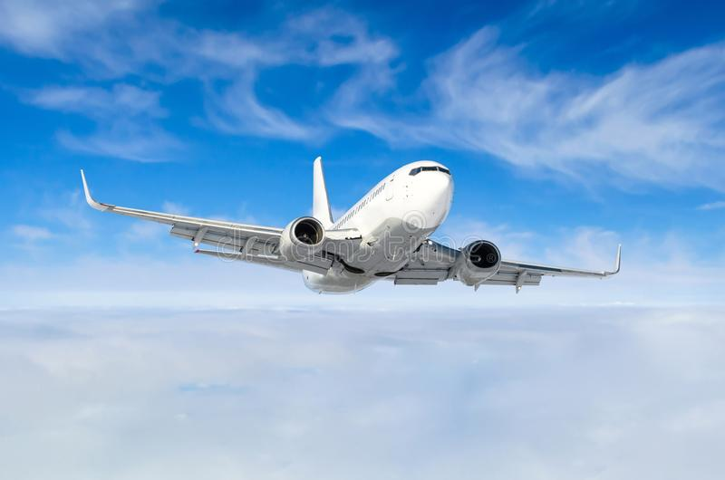 White aircraft flies climbs height, flight level high in the sky above the clouds blue sky. stock photo