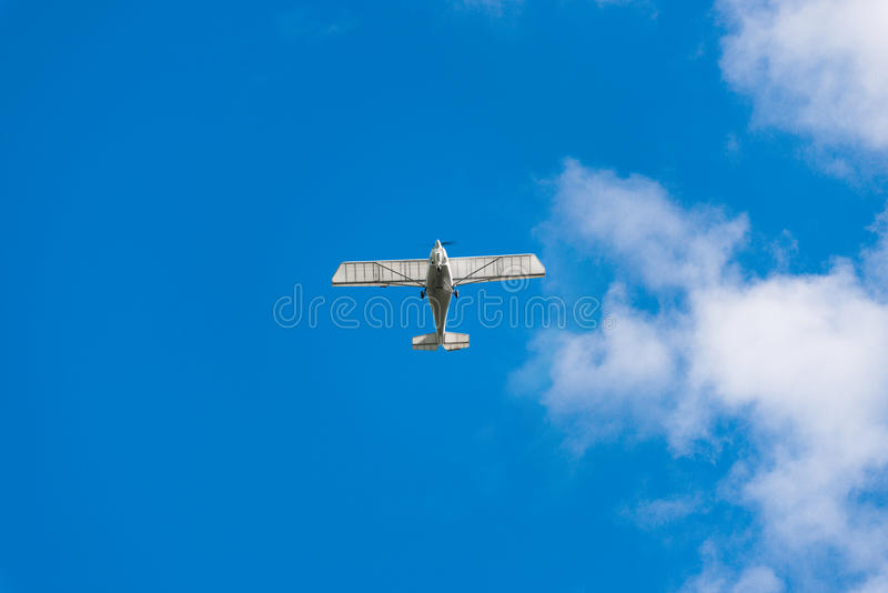 White airplane and blue sky. Small passenger plane flying in the blue sky. Light-engine aircraft and blue sky.Airplane in the sky stock photo