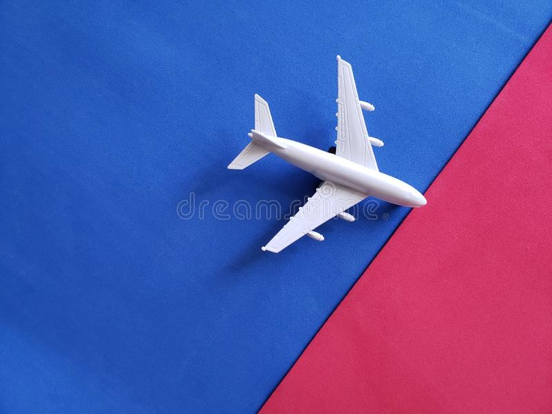 White airplane figure with red and blue background. White airplane figure red blue background transport transportation airline airport aviation backdrop top view stock photo