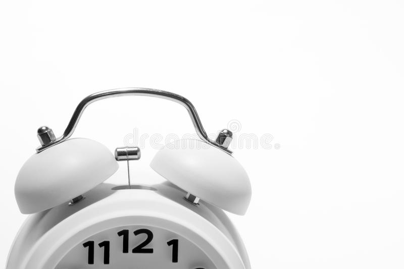 White Alarm Clock. A white analog/mechanical alarm clock with the numbers 11,12 & 1 visible on the clock-face stock images