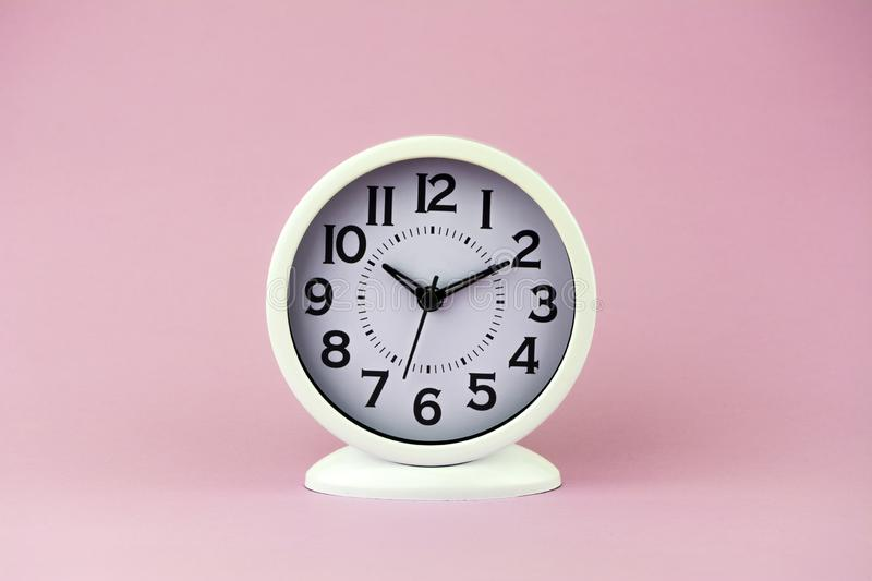 White alarm clock with big numbers on pink background.  stock photography