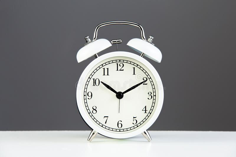 White alarm clock. On a gray wall background. Interior details. Classic clock for the interior royalty free stock photos