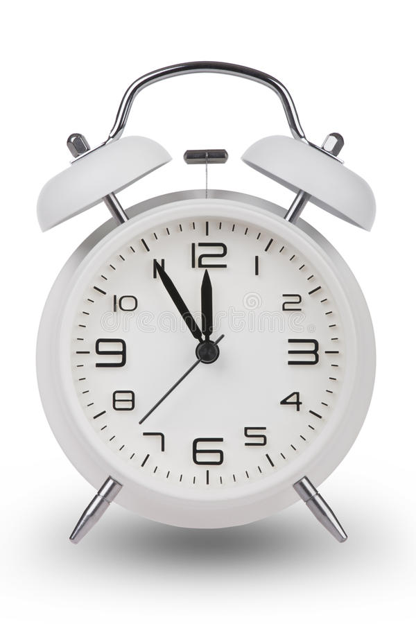 White alarm clock with hands at 5 minutes till 12. White alarm clock with the hands at 5 minutes till 12. Illustrating Time is Running Out isolated on a white royalty free stock image