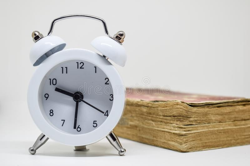 White alarm clock and Old book (Dictionary) on white background. Time cannot be reversed And knowledge has no end date alert arrow bell circle stock photo