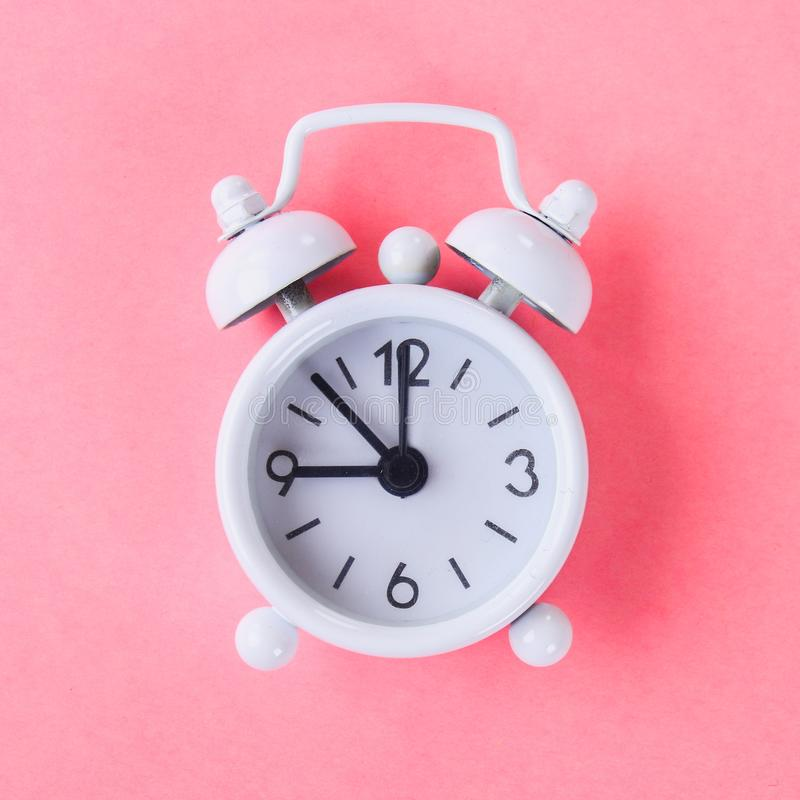 White alarm clock on a pastel blue, pink background. White alarm clock on a pastel blue, pink background royalty free stock image