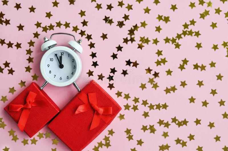 White alarm clock with red gift and star confetti on pink delicate background for holiday time stock photos