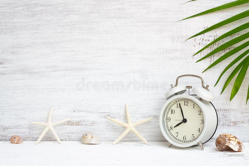 White alarm clock with starfish, sea shells and green palm leaf background. Background concept for Summer time holiday vacation. Abstract background for royalty free stock image