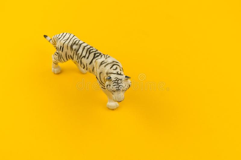 White albino tiger toy made of plastic on a yellow background. African animal for a child stock photos
