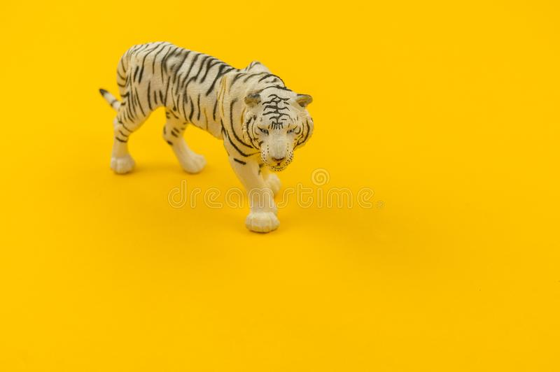 White albino tiger toy made of plastic on a yellow background. African animal for a child royalty free stock photo
