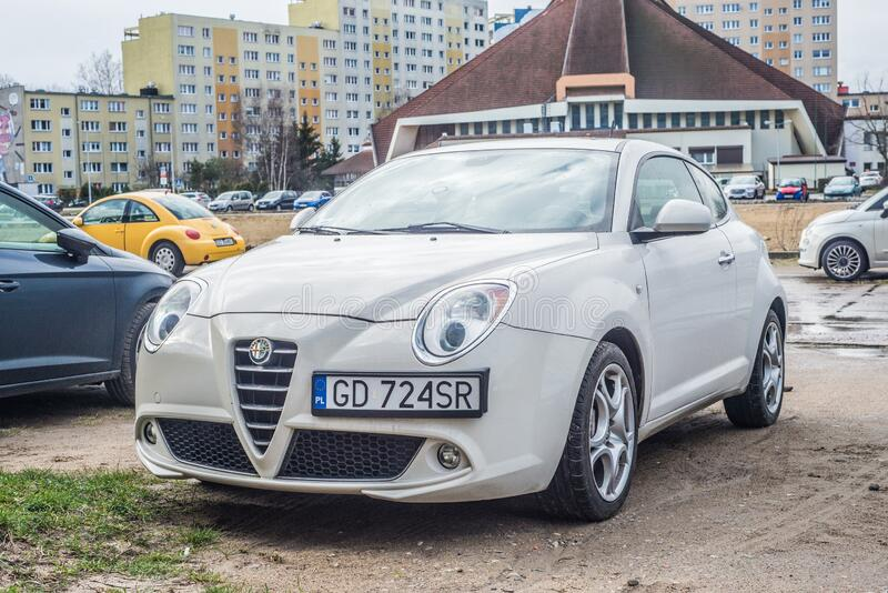 White Alfa Romeo Mito parked. In Gdansk Zaspa in northern Poland. Left side and front view. Old post communist blocks of flats in the background stock images