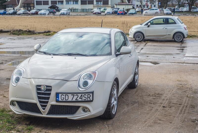 White Alfa Romeo Mito parked. In Gdansk Zaspa in northern Poland. Left side and front view. Old post communist blocks of flats and new Fiat 500 in the stock photos