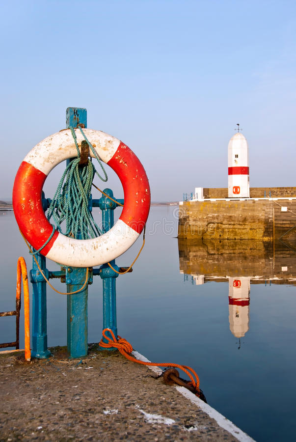 Free White And Red Life Buoy In Harbour With Lighthouse Royalty Free Stock Images - 19666419