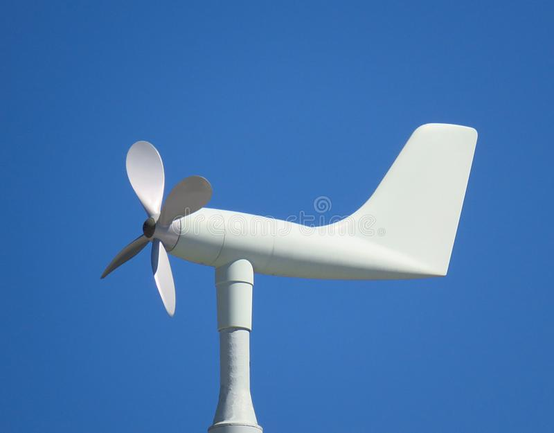 White anemometer wind vane on blue sky background stock image