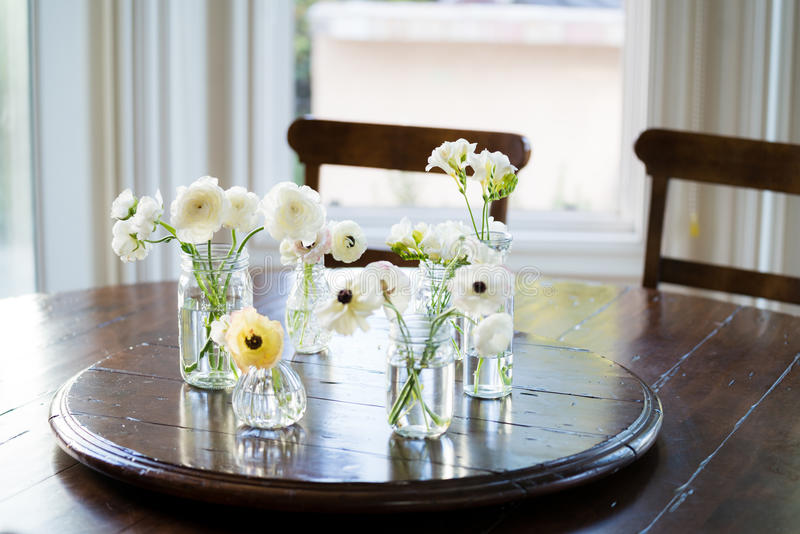 White Anemones and Ranunculus on Dining Room Table. A collection of white flowers including anemones and ranunculus stock photography