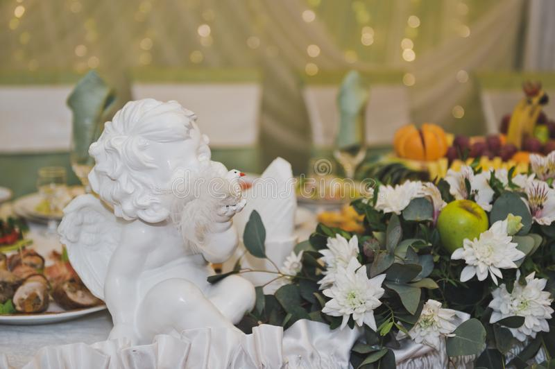 Plaster statuette of an angel as decoration 8837. White angel amongst the flowers on the holiday table royalty free stock photography
