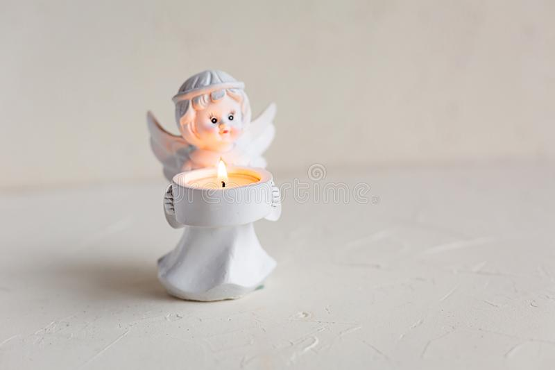 White angel candleholder with lighted candle on white. Small candleholder of an angel with a lighted candle on white concrete background. Holiday, greeting card stock photo