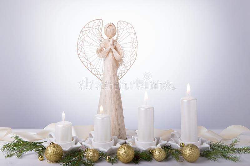 A white angel and four white Advent candles, Christmas tree branches are decorated with golden balls. The imminent. Background of Advent and Christmas royalty free stock images