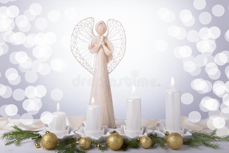 A white angel and four white Advent candles, Christmas tree branches are decorated with golden balls. The imminent. Background of Advent and Christmas royalty free stock photos